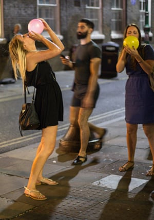 Revellers take laughing gas in an east London street where it is openly sold for around £3 a go.