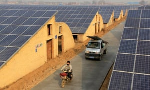 A resident on an electronic bicycle and a truck travel past solar panels on the roof of greenhouses growing mushrooms in Neihuang county, Henan province