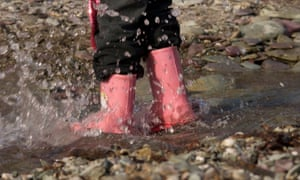Child standing a puddle wearing wellies