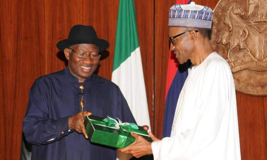 Outgoing Nigerian President Goodluck Jonathan (left) presents a gift to President-elect Muhammadu Buhari (right) in Abuja, Nigeria.