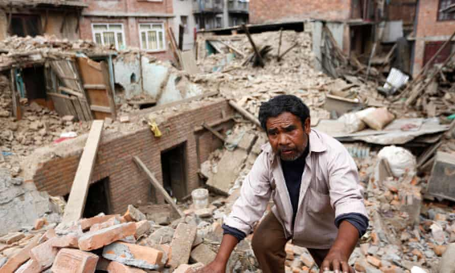 A man climbs in the ruins of his damaged home in Lalitpur – many earthquake victims have not received food, shelter and water in remote areas a week after the earthquake.