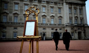 Two workers return to Buckingham palace after placing an easel in the forecourt to announce the birth of a baby girl to the Duchess of Cambridge.