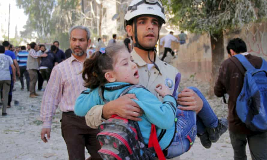 A civil defence worker rescues a schoolgirl after what activists said was a barrel-bomb attack by forces loyal to Syria's president Bashar al-Assad in Aleppo.