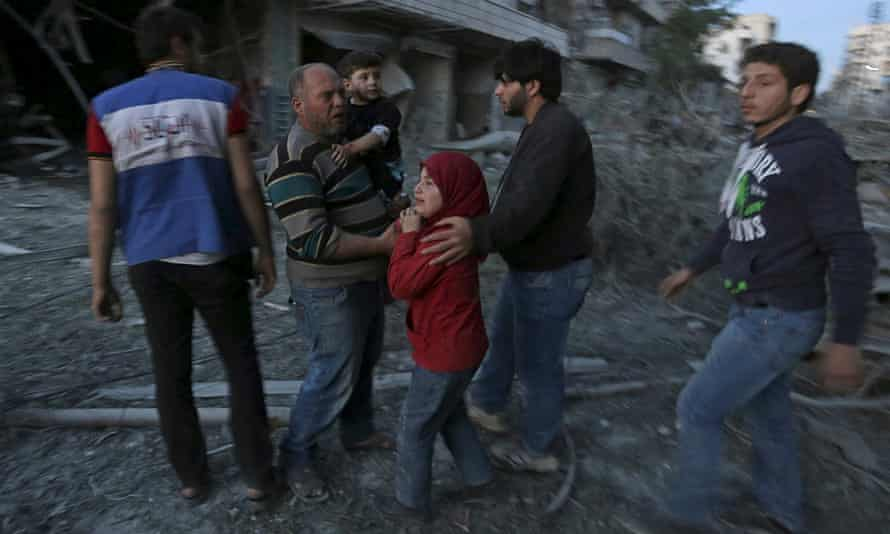 A family amid wreckage in the wake of an attack in Aleppo on Friday.