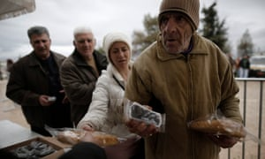 People receive olives and bread distributed for free by municipality of Athens in February. After three months of fruitless talks, Greek public finances have never been worse.