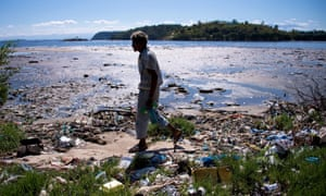A man walks along the shoreline of the polluted waters of Guanabara Bay near Rio de Janeiro. The iconic bay will be the site of sailing events during the 2016 Olympic Games.