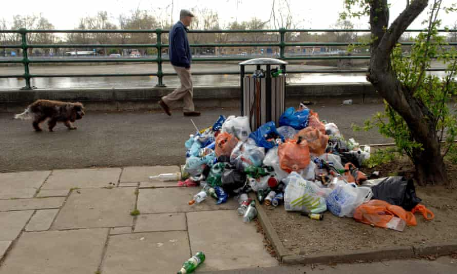 Litter piled by an overflowing bin along the Thames in west London