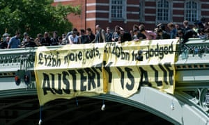 Demonstrators display a banner on Westminster Bridge as they participate in a protest against the British Government's planned austerity measures in central London