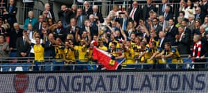 Arsenal celebrate with the trophy.