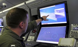A US navy crewman aboard a surveillance aircraft views a computer screen purportedly showing Chinese construction on the reclaimed land of Fiery Cross Reef.