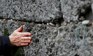 A survivor touches the Wall of Death in the former Auschwitz concentration and extermination camp.