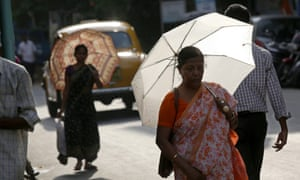 Indian commuters use umbrellas to stay cool in oppressive conditions.