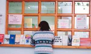 A woman waits at a GP surgery