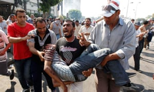 Protesters who support former Egyptian President Mohamed Mursi carry an injured man during clashes outside the Republican Guard building in Cairo July 5, 2013.