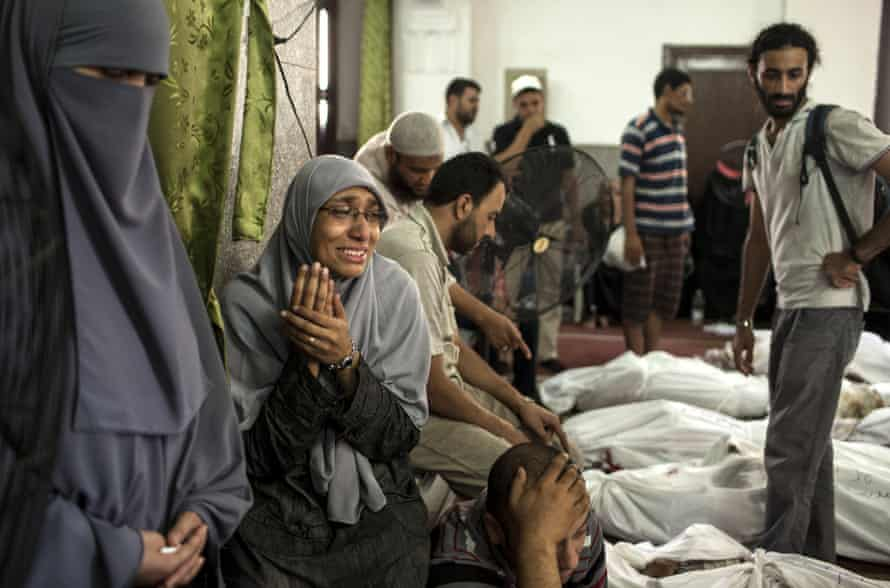 An Egyptian woman identifies the body of a family member, a supporter of deposed Egyptian President Mohammed Morsi killed during a violent crackdown by Egyptian Security Forces on pro-Morsi sit-in demonstrations the day before, at the al-Iman Mosque in Nasr City on August 15, 2013 in Cairo, Egypt.