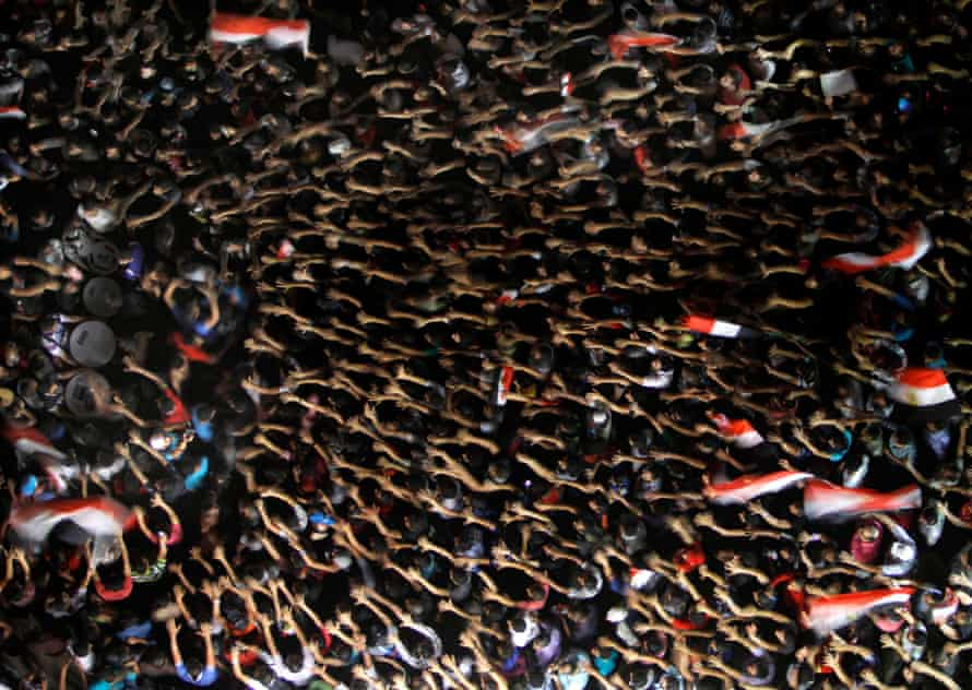 Egyptian protesters wave their hands and hold national flags during anti-President Mohammed Morsi demonstration in Tahrir Square in Cairo on June 28, 2013.
