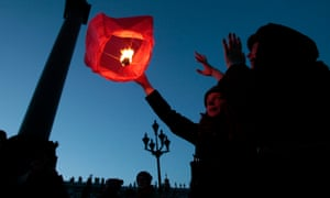 People launch a paper lantern during a ceremony to mark Earth Hour at Palace Square in St Petersburg, Russia.