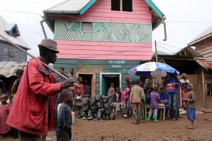 3 April 2015. Numbi, DRC  A local vodacom sales booth under a blue and white umbrella in front of the pink Restaurant Salama on Numbi's muddy main strip . With earsplitting crackling sound blaring out of old speakers, a salesman takes to the microphone selling credit for the upcoming phone service.