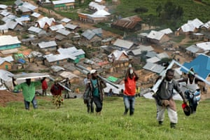 2 April 2015. Numbi, DRC The last pieces of kit have arrived in Numbi and are being carried up to the top of the hill for the installation of the phone tower.  Note the solar panels . Numbi town looks tiny below.drcsusan