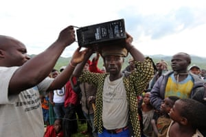 2 April 2015. Numbi, DRC  Buckling and sweating under the heavy weight of the piece of kit he has been carrying for hours and hours walking up steep hills, the porter arrives with one of the four 50kg batteries.