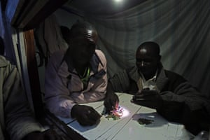 1 April 2015, DR Congo . NumbiMineral buyers/vendors examine their tantalum gems by flashlight at night in their kiosk.