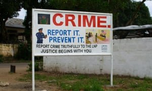 Sign urging people to report crimes to the Liberia National Police
