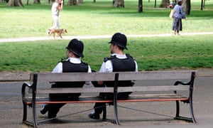 Two police officers enjoy the sunshine, safe in the knowledge that crime is falling as they relax.