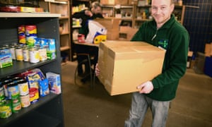 Michael Spence a volunteer packs food at a food bank  in Whitburn, Scotland.