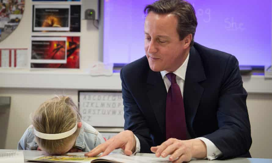 Prime Minister David Cameron helps with a reading lesson at the Sacred Heart Roman Catholic Primary School in Westhoughton
