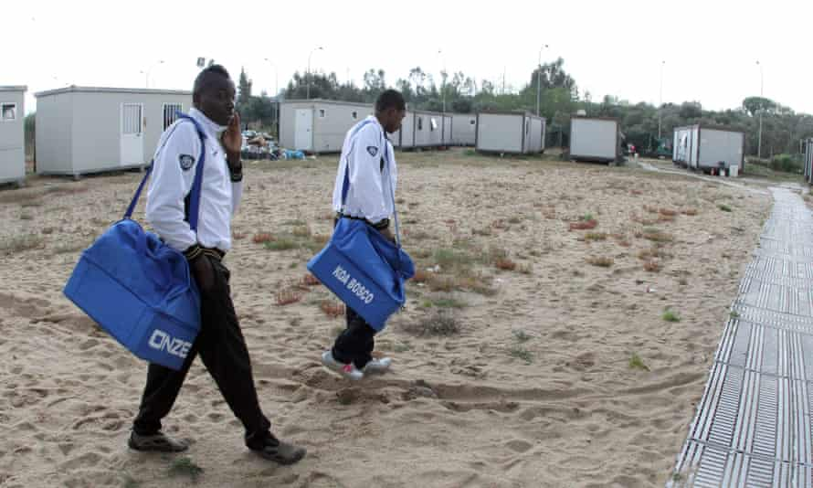 Koa Bosco captain Yaya Diallo, from Ivory Coast, right, and his team-mate Ali Trauri leave their tent camp for a training session in San Ferdinando.