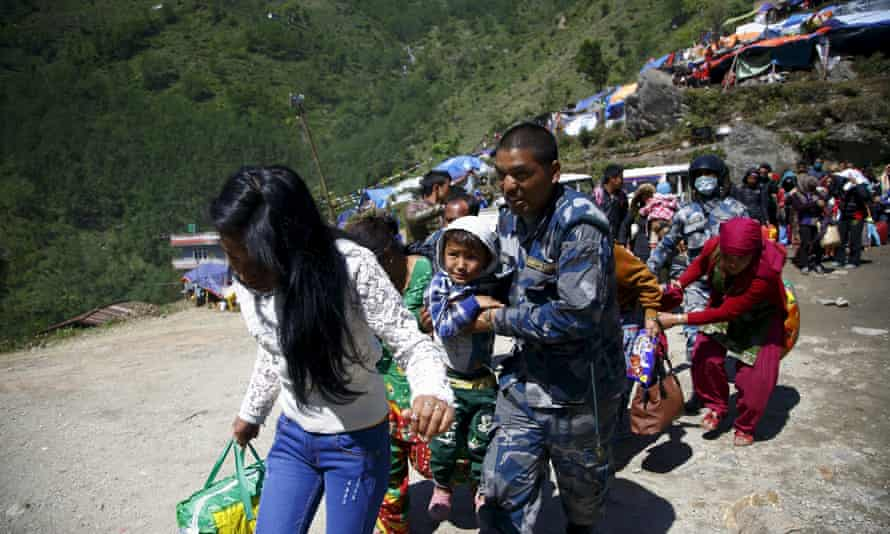 Armed Nepalese police help people in Sindhupalchok district board a helicopter to Kathmandu after last month's earthquake.