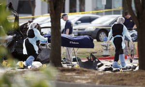Personnel remove the bodies of two gunmen who opened fire on a security officer on Sunday outside a venue in Dallas, Texas.