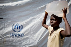 A young girl carries water at the reception centre. More than 23,000 people, mainly women and children, have fled from Burundi into Rwanda since the beginning of April, according to the UNHCR.