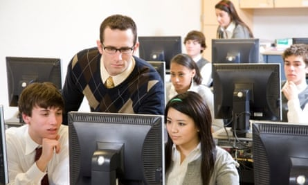 A teacher with pupils in a computer room
