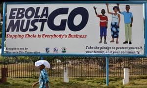 A man walks past an ebola campaign banne