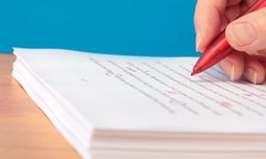 proofreader marking a document with red pen