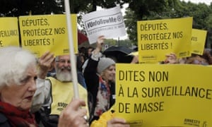 "Demonstrators hold placards reading ""Stop to Mass Surveillance"", and ""Members of Parliament Protect our Freedom"", during a gathering at Invalides, Paris, to protest against the emergency government surveillance law"