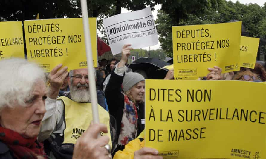 """Demonstrators hold placards reading """"Stop to Mass Surveillance"""", and """"Members of Parliament Protect our Freedom"""", during a gathering at Invalides, Paris, to protest against the emergency government surveillance law"""
