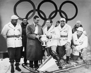 German bobsledder Werner Zahn presents the Olympic trophy to Fiske, while the rest of the four-man winning American bobsled team looks on.