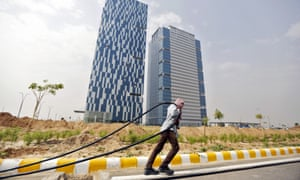 A labourer pulls a cable in front of office buildings in Gujarat International Finance Tec-City (Gift City).