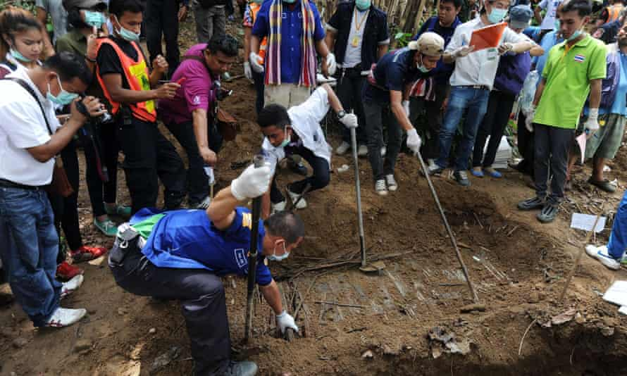 Rescue workers and forensic officials dig out skeletons from shallow graves covered by bamboo at the site of a mass grave at an abandoned jungle camp in the Sadao district of Thailand's southern Songkhla province bordering Malaysia on May 2, 2015. The badly decayed remains of at least three more migrants thought to be from Myanmar or Bangladesh were exhumed on May 2 from a mass grave in southern Thailand, as details emerged of the maltreatment endured at the remote people smugglers' camp.