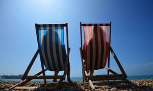 Two people sitting in deckchairs on the beach