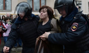 Russian police officers detain an opposition activist outside a court in Moscow.