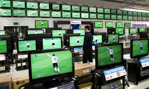 An employee checks the pricing on televisions whilst the football World Cup is shown at a Currys store in London