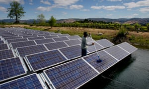Elbin Blatz washes off one of 994 panels in the floating solar cell array at Far Niente winery in Oakville, California