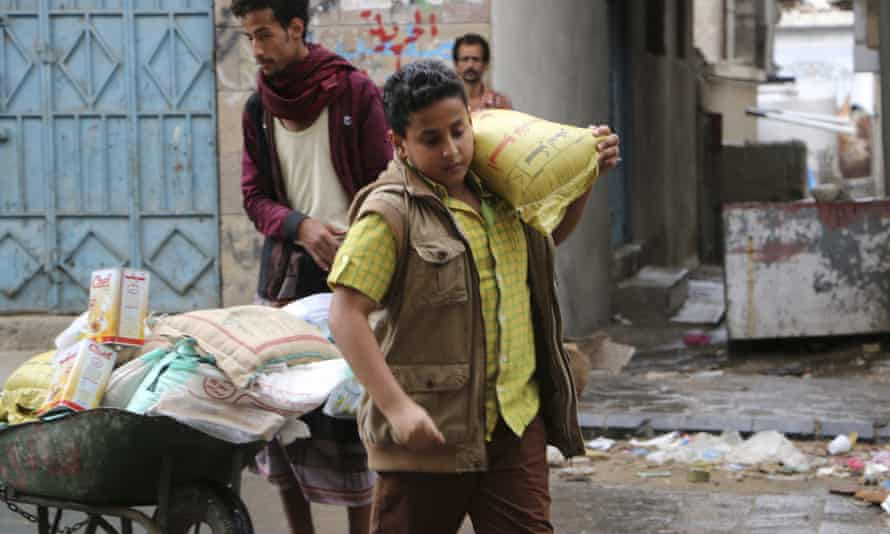 A boy carries a bag of sugar to his family during  food distribution by Yemeni volunteers in Taiz.