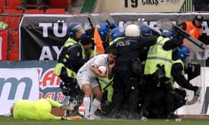A Bursaspor player hides from the objects thrown by Diyarbakirspor fans, as an injured assistant referee lays on the pitch, during the Super League soccer match in Diyarbakir in March 2010.