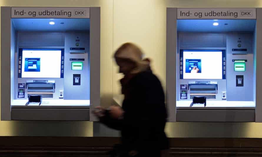 A woman passes cash-machines in downtown Copenhagen.
