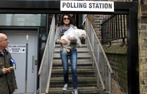 A woman leaves a polling station in Islington, carrying her dog