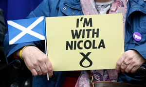 An SNP supporter holds a sign